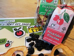 Dried apple rings and cherries are scattered across a table with the packets next to them