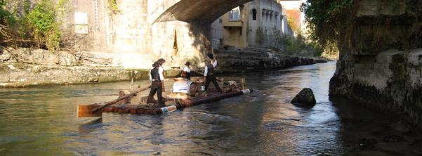 Men in historic dress travel under a bridge on a raft